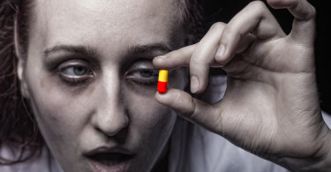 Young woman holding a pill addict. Focus on hands ** Note: Shallow depth of field